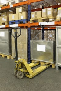 Manual pallet truck in distribution center warehouse