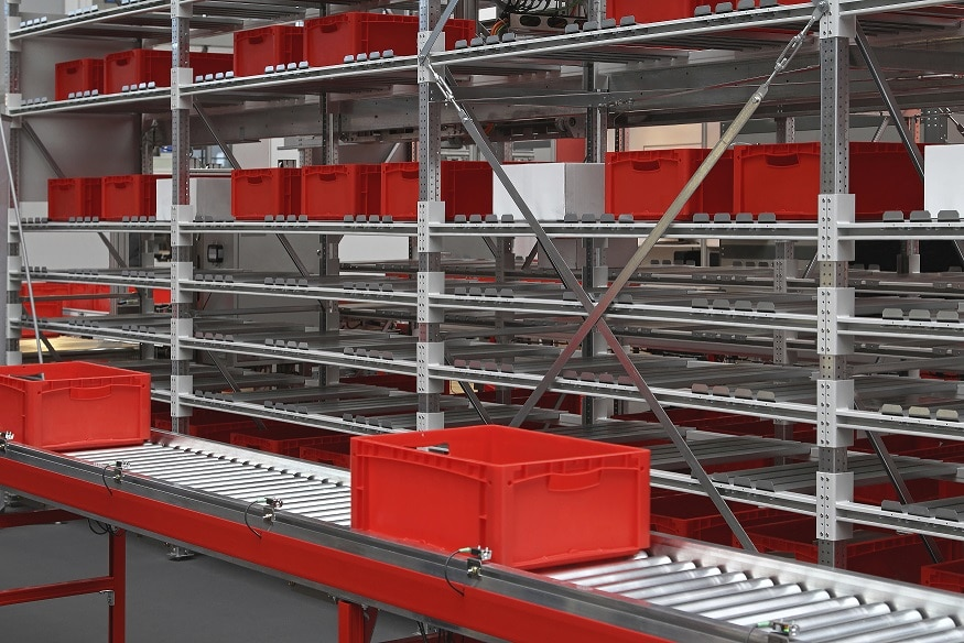 Red crates at conveyor rollers in distribution warehouse